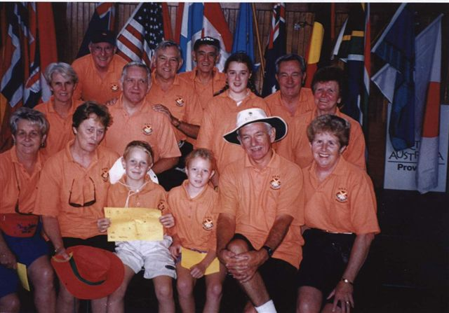 A photo of adults and children in orange shirts.
