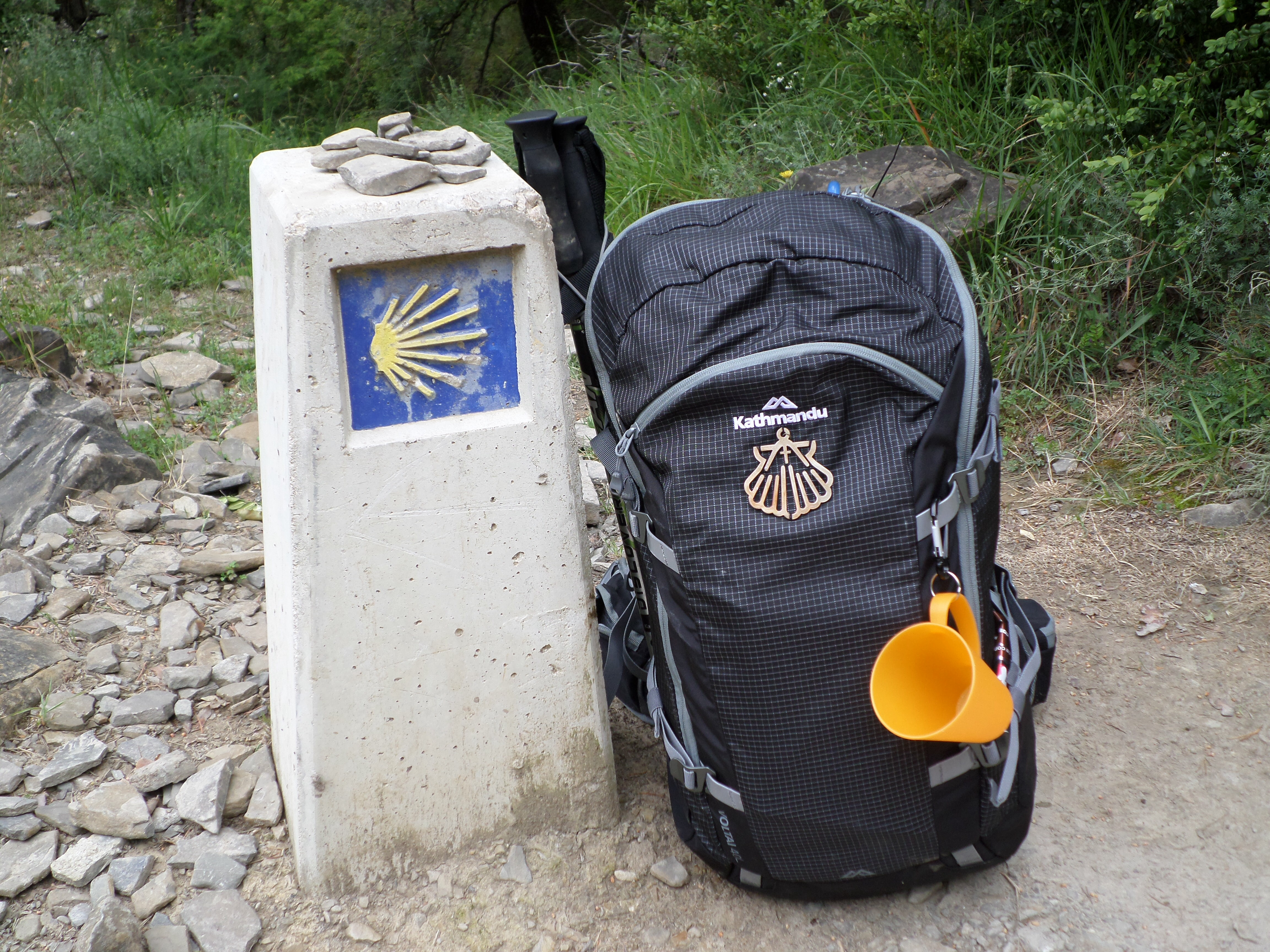 Photo of a concrete walk marker with scallop and a backpack.