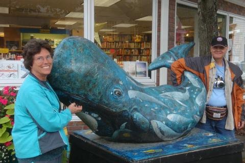 Photo of a man and a woman on either side of a whale sculpture in Mystic, CT.