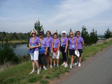 A photo of seven women wearing purple shirts on the shore of Lake Burley Griffin.