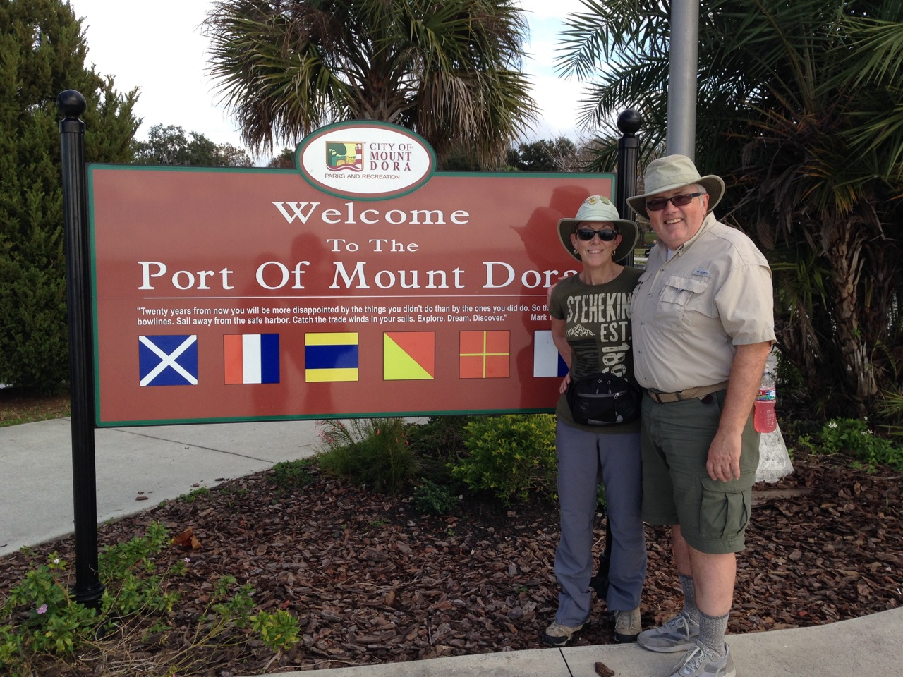Man and woman standing in front of sign for Port of Mount Dora.