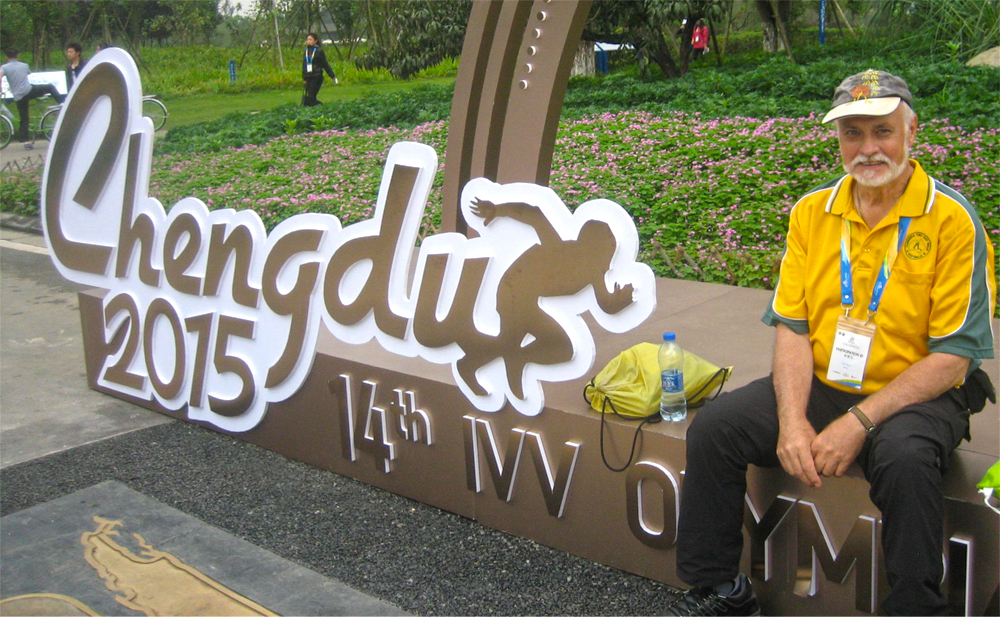 Photo of man sitting next to sign that says Chengdu 2015.