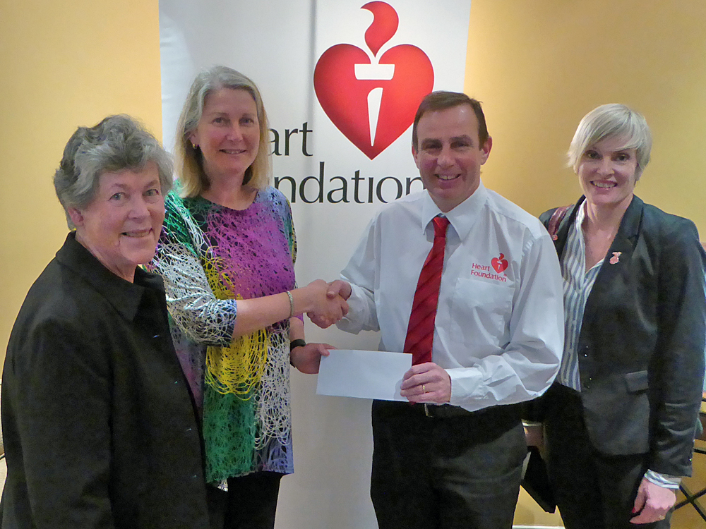 Two women from Canberra Two Day Walk presenting a cheque to two Heart Foundations administrators.