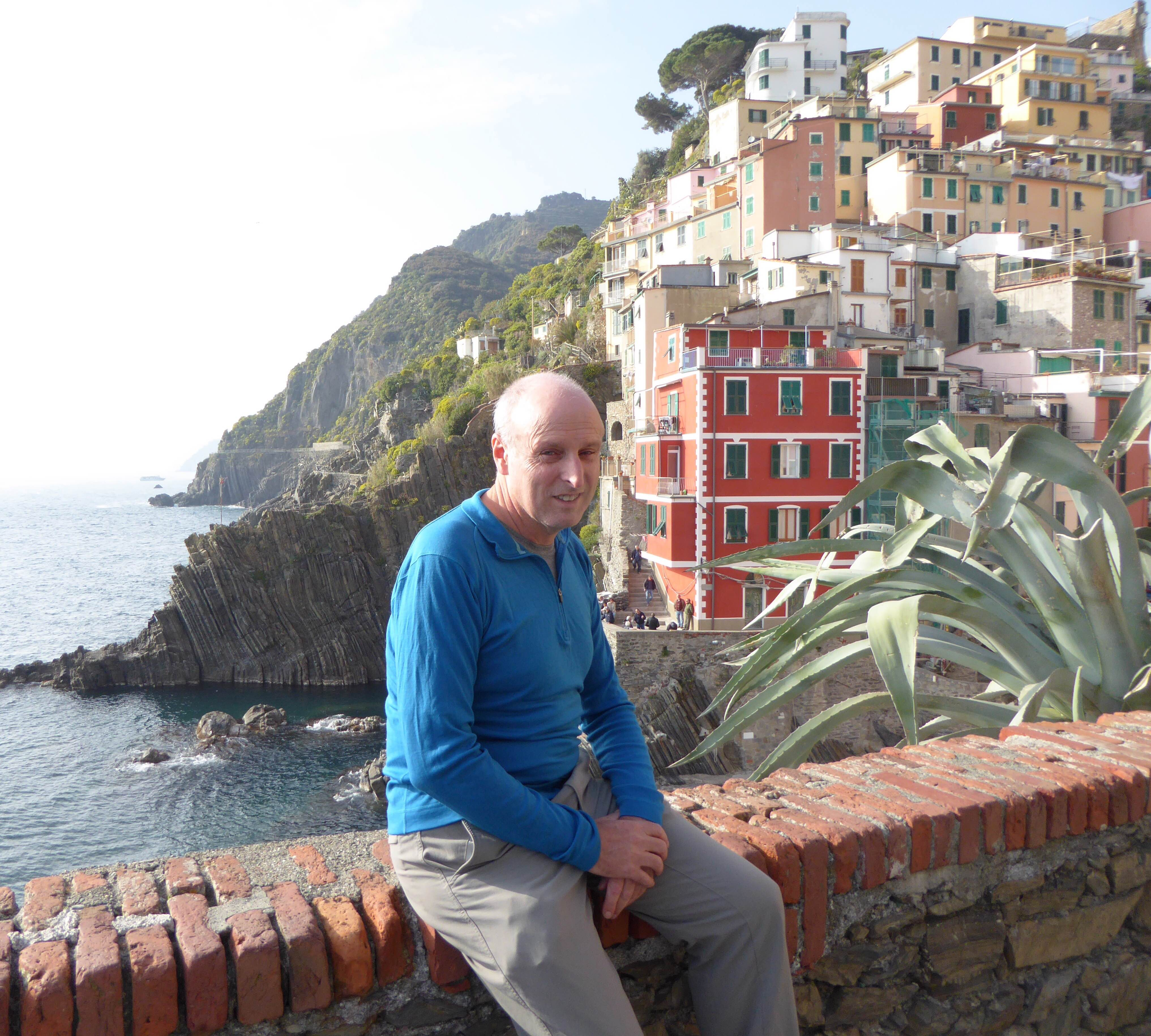 A man sitting on a wall in Cinque Terre, Italy.