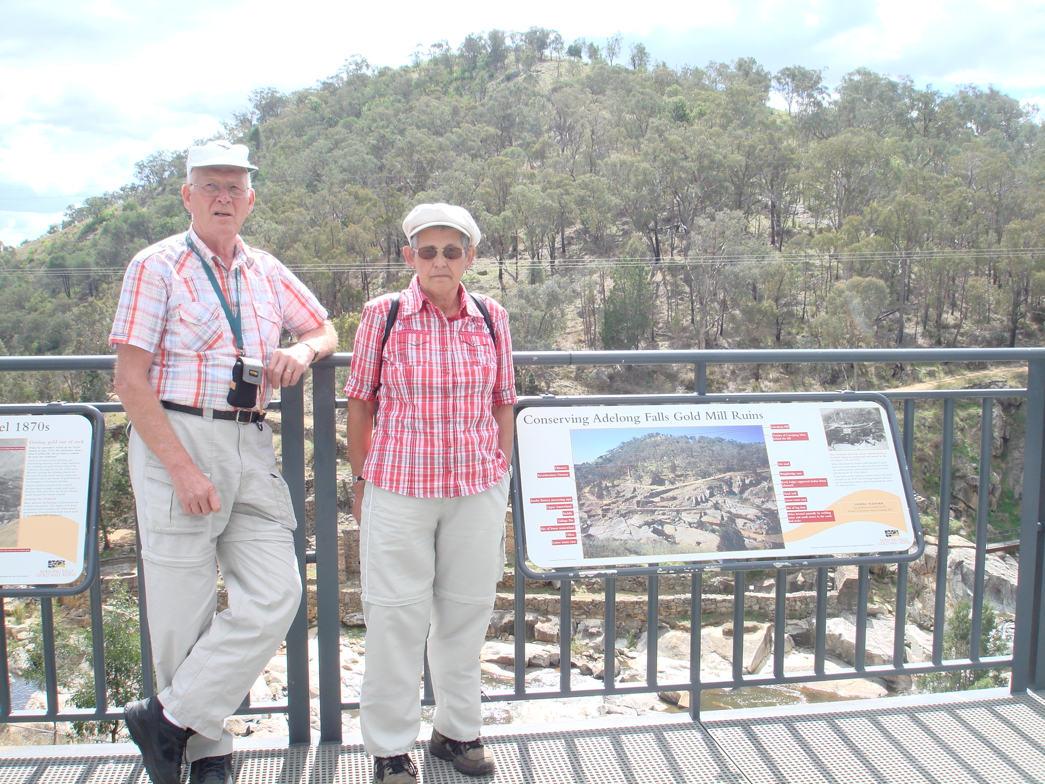A man and a woman in front of a sign for Adelong Falls Gold Mill Ruins.